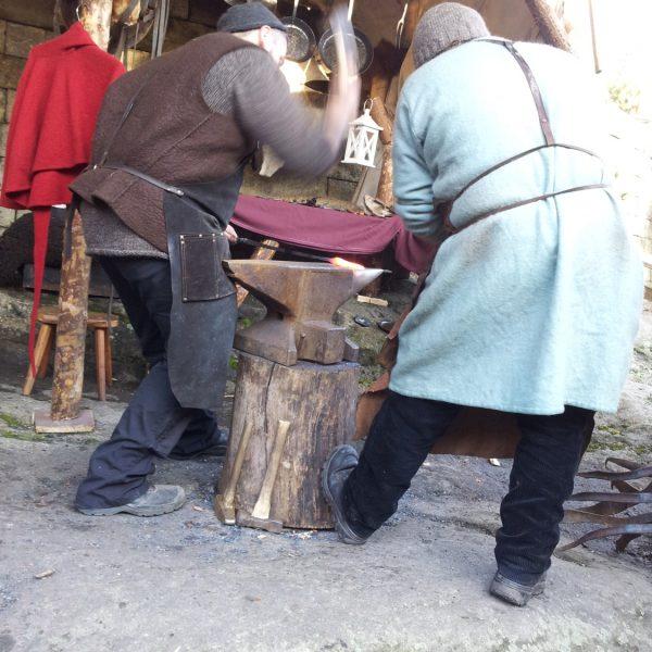 Zwei Schmiede bearbeiten ein glühendes Metallstück auf dem Weihnachtsmarkt der Festung Königstein