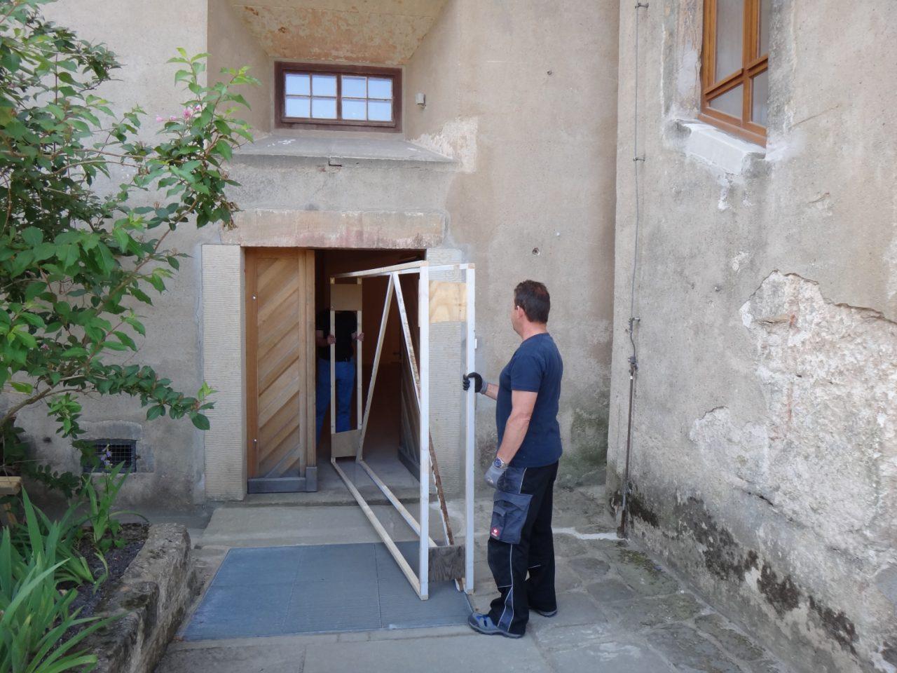 Mitarbeiter mit Holzrahmen vor der Tür der Magdalenenburg