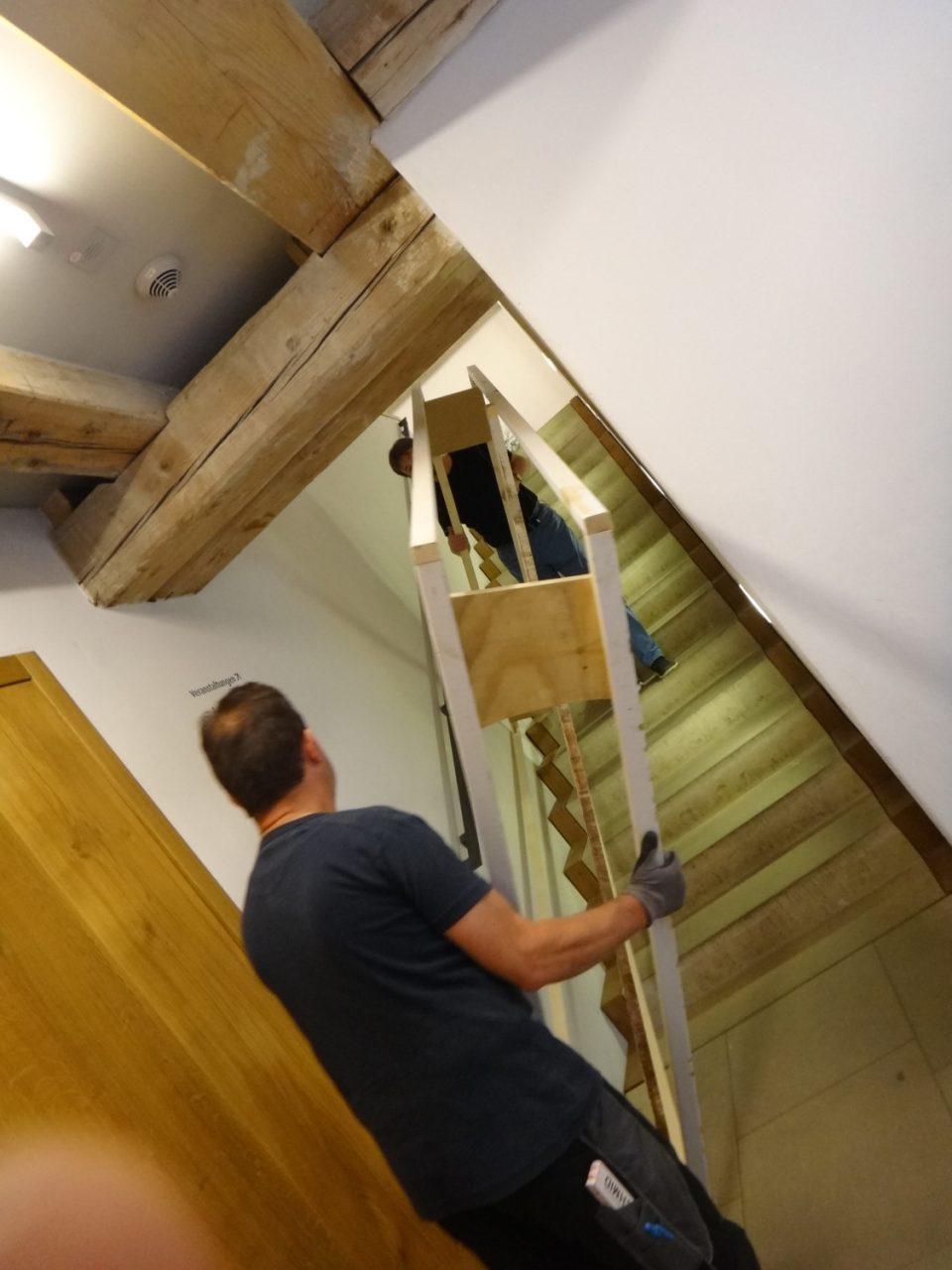 Mitarbeiter tragen den Holzrahmen die Treppe hoch