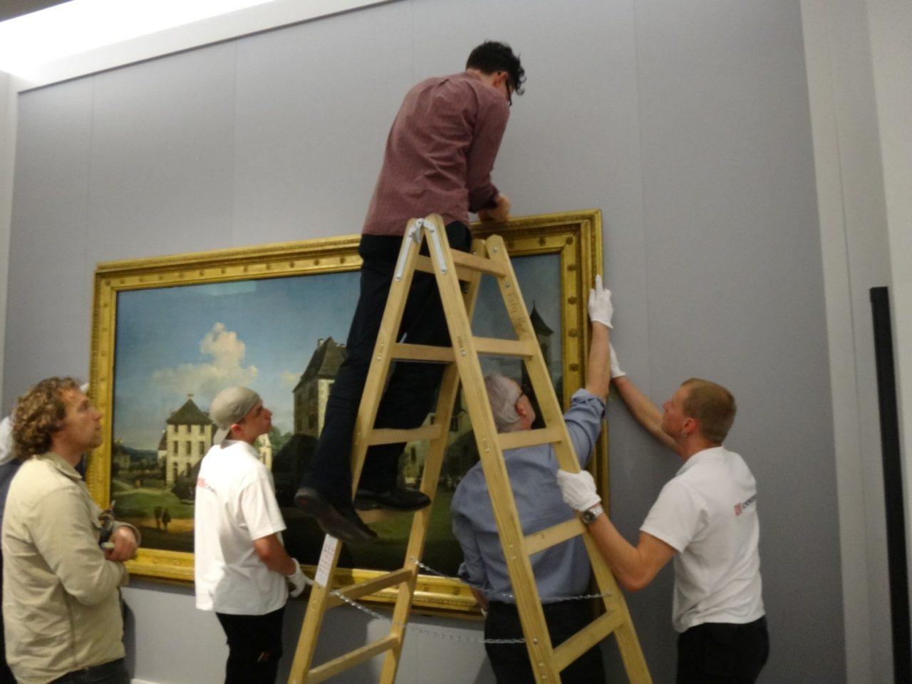Restaurator Adam auf der Leiter vor dem Gemälde