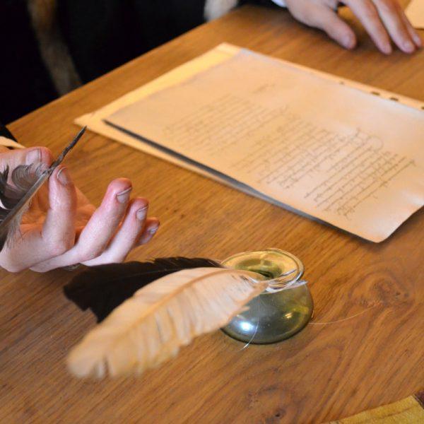 Hände, Schreibfedern und Blätter auf Schreibtisch