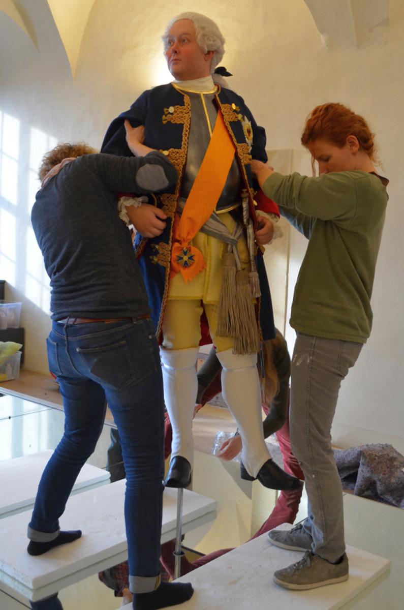Die Figur Friedrich Wilhelms wird von Figurenbauerin und Kostümbildnerin auf das Spiegelpodest montiert
