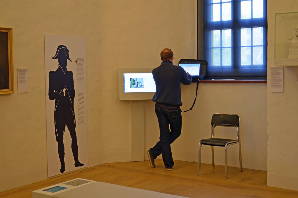 Sven Dietrich mit Laptop an der Medienstation (Bildschirm)