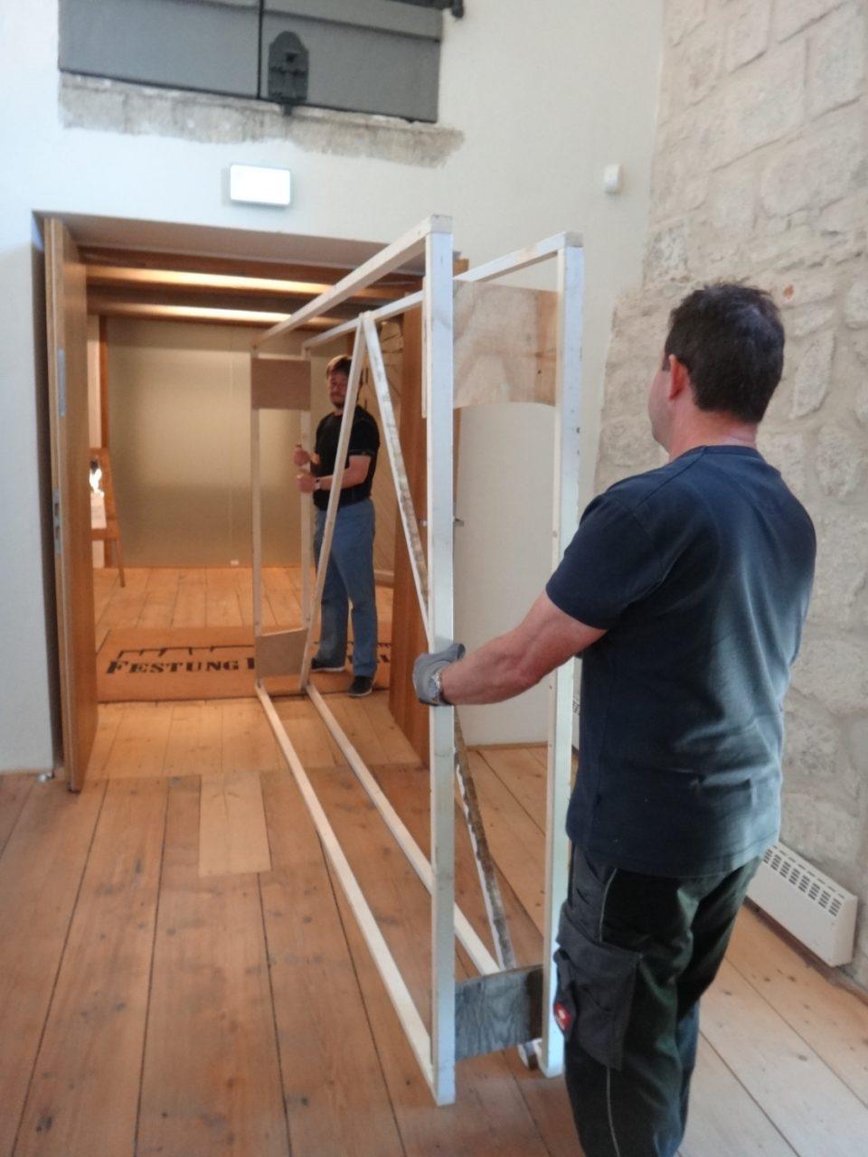 Mitarbeiter mit dem Holzrahmen vor der vorletzten Tür