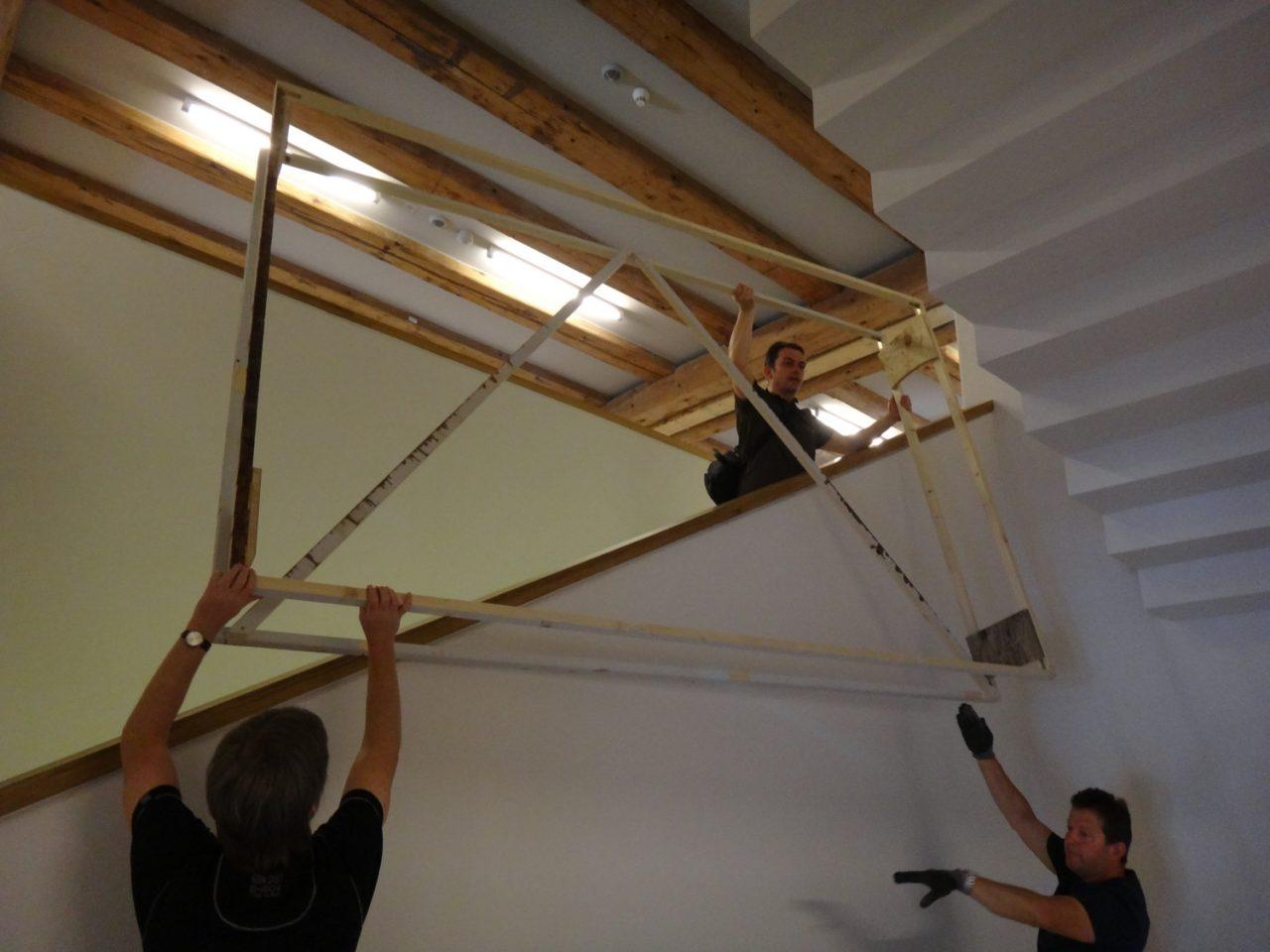 Holzrahmen wird durchs Treppenhaus gereicht.