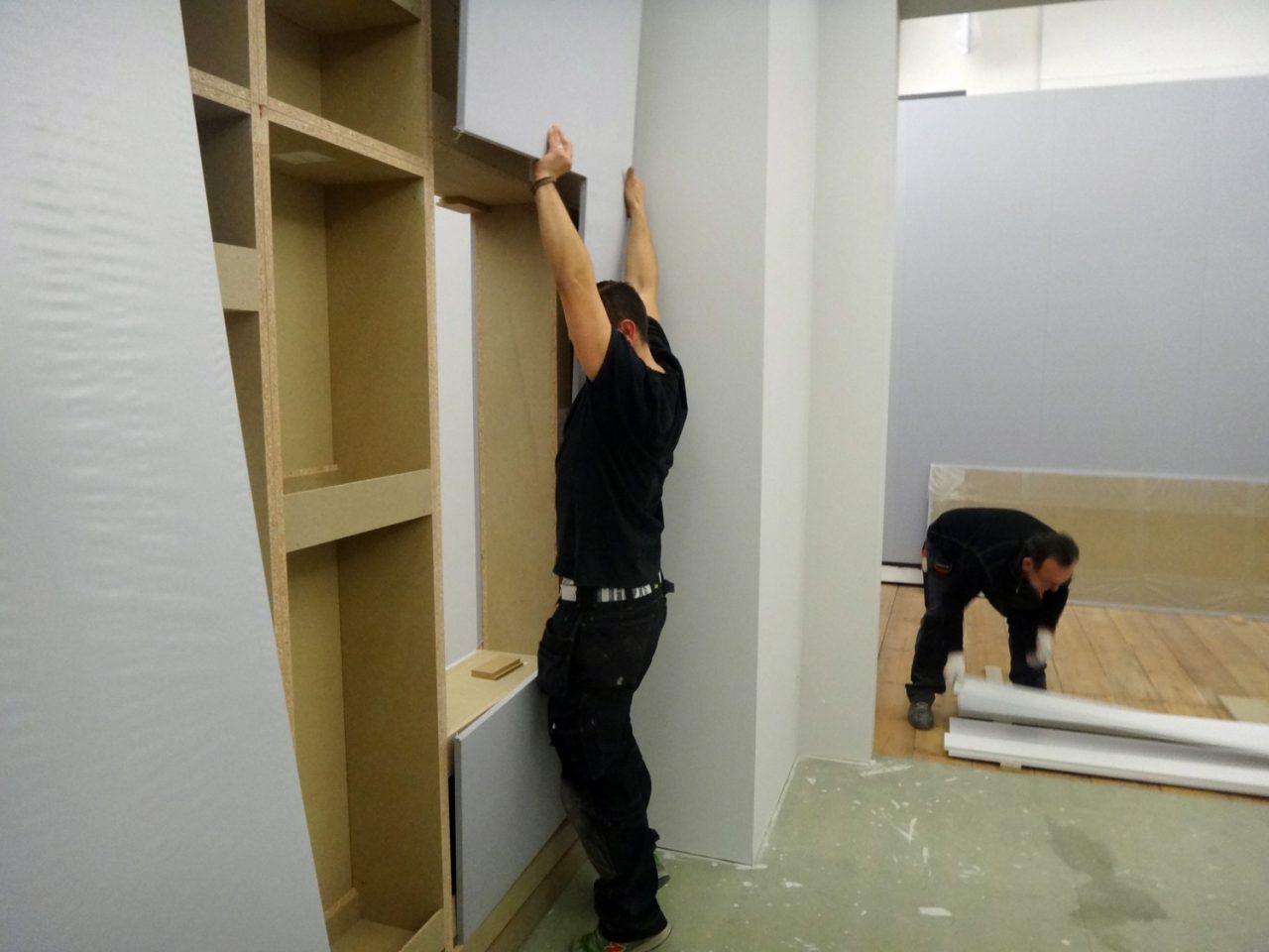 Handwerker passt Wandverkleidung ein