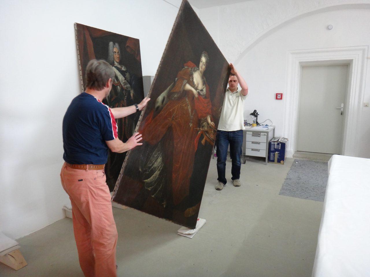 Mitarbeiter beim Aufstellen der zu rahmenden Gemälde