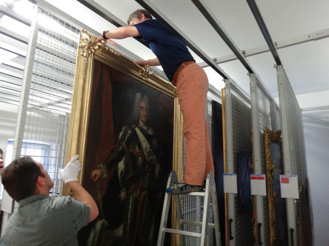Mitarbeiter hängen Gemälde in die Zugdepotanlage