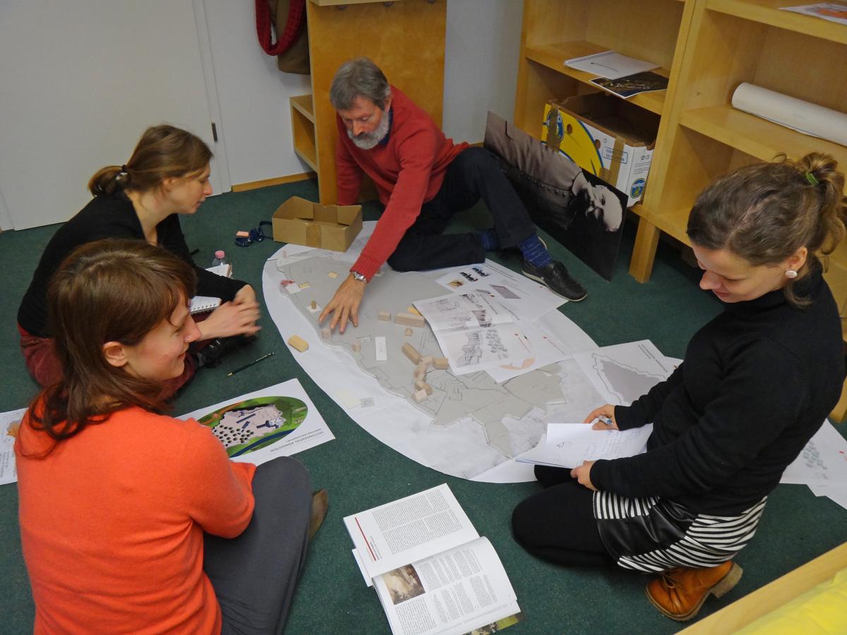 Die 4 Projektmitarbeiter sitzen um das Arbeitsmodell der Festung herum