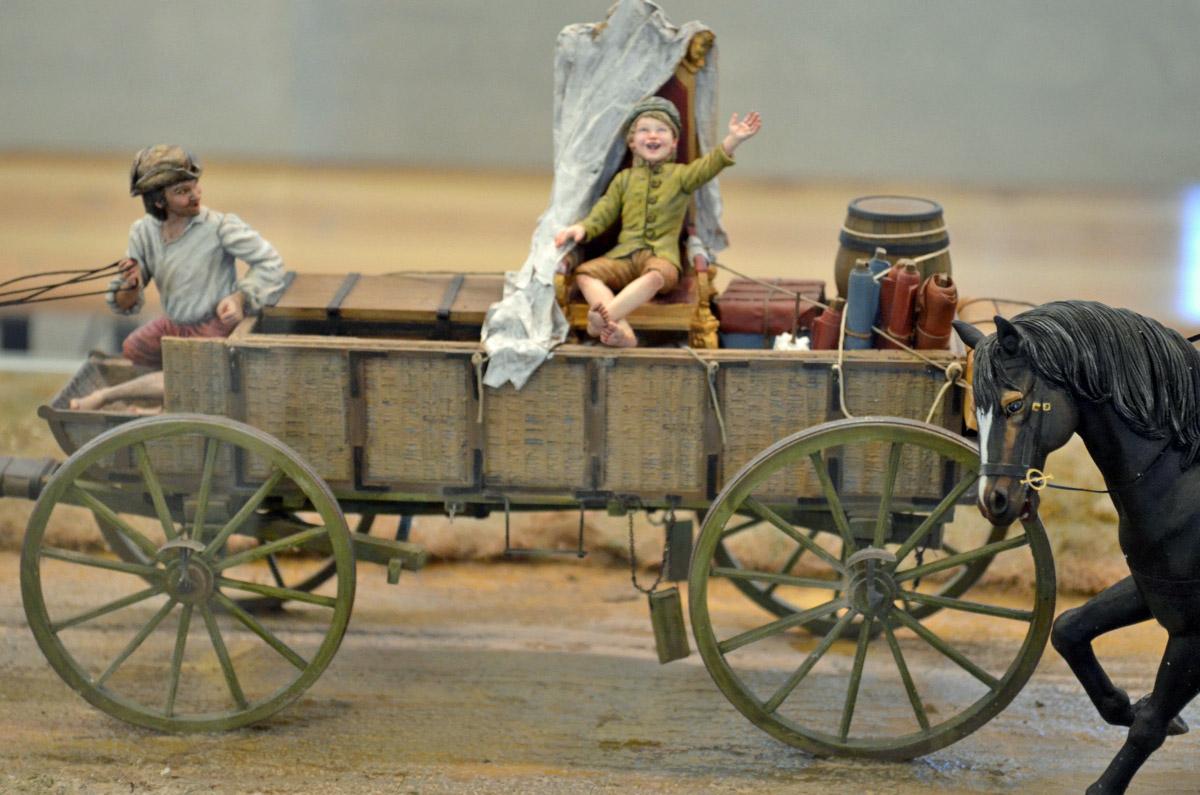Bauernjunge auf großem Stuhl, der auf einem Wagen transportiert wird