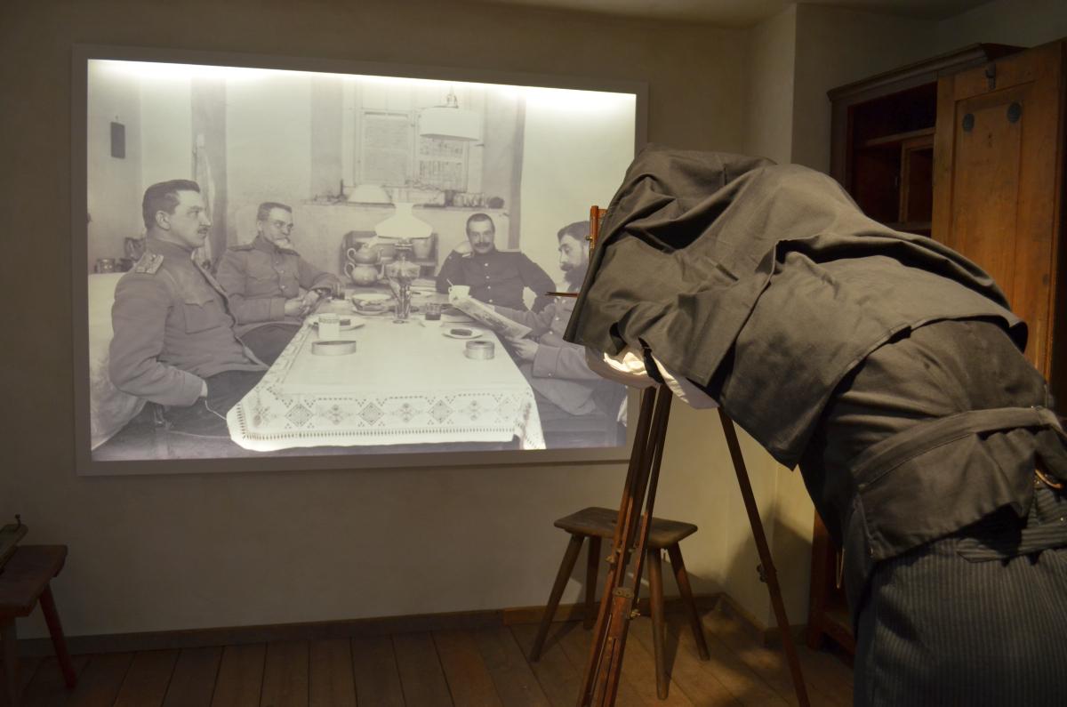 Fotograf mit Plattenkamera vor einem Foto aus dem 1. Weltkrieg