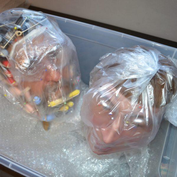 Zwei in Tüten verpackte Köpfe