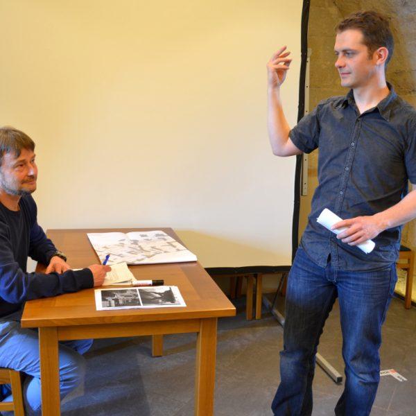 Zwei Mitarbeiter mimen die Szene des Architektengesprächs