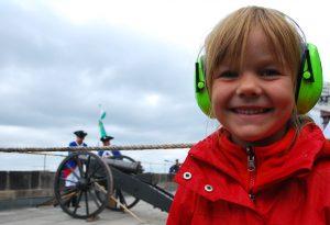Kind mit Ohrenschützern vor Kanone